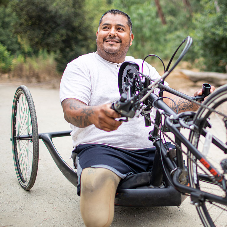 man smiling and sitting on a handcycle