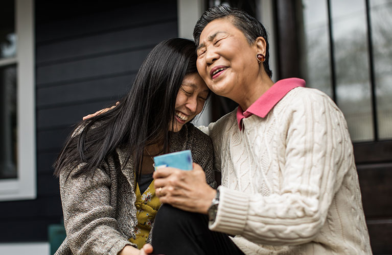 two women on a porch smiling and embracing