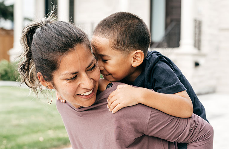 woman smiling and giving piggyback ride to child